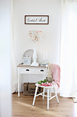 Pink tulips and wooden bunny on a white chair in front of a table with drawer