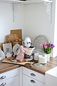 Food processor, scales, rabbit figure, glass vessels and tulips on the kitchen worksurface