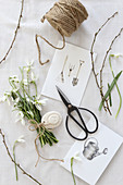 Snowdrops, scissors, drawings and string on a white surface