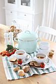 Suppenterrinen, Kochtopf und Gemüse auf Esstisch
