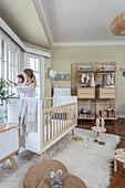 Mutter mit Kleinkind am Fenster im Kinderzimmer mit Gitterbett auf Hochflorteppich