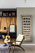 Designer chair with fur blanket, guitar in front of fitted cabinets and vintage eye chart on the wall