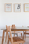 Designer chairs and dining table below modern prints on the wall