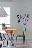 Delicate dining table and chairs: pin board in the background