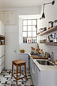 Narrow kitchen with white subway tiles, wooden shelves, lattice windows and wooden stool