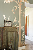 Vintage cabinet in room with mural of tree on wall