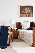 Stuhl und antiker Nachttisch mit Leuchte neben Bett mit Bettkopf aus Holz