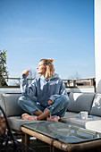 Blonde woman in casual wear is sitting on the terrace