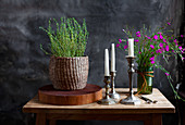 Bouquet of wild Carthusian pinks and grass, basket of thyme on a wooden disc and silver candle holder