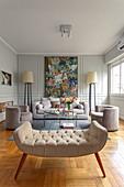Helle Polstermöbel, Stehleuchten und Gemälde an Wand mit Kassettenverkleidung im Wohnzimmer