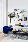 Niedriger Couchtisch, blauer Sessel und weißes Sofa, darüber Regale im Wohnzimmer