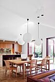 Essbereich mit Holztisch und Klassikerstühlen, darüber Lampen mit Papierschirm