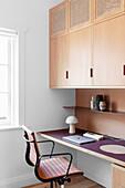 Arbeitszimmer mit Einbauelementen und Klassikerstuhl