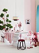 Weihnachtstisch in Rosa und Weiß, im Hintergrund verpackte Weihnachtsgeschenke