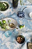 Limetten, Salat und Schälchen auf blau-weißer Tischdecke