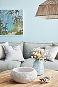 Coffeetable mit Schale und Vase vor hellgrauem Posltersofa