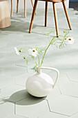 Vase mit Cosmea auf Wabenfliesen
