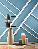 Blaue Wand mit Gipsrahmen dekoriert, davor Coffeetable mit Vase