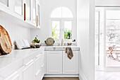 Weiße Einbauküche in L-Form mit Rundbogenfenster
