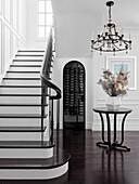 Eingangshalle mit Treppenaufgang, runder Tisch mit Blumenstrauß und Kronleuchter