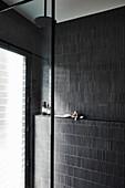 Duschbereich mit schwarzen Wandfliesen
