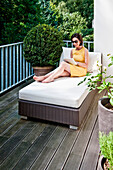 Woman sitting on a lounger while using an iPad on a balcony, Hamburg, Germany