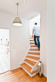 Man walking up the stairs, House furnished in country style, Hamburg, Germany