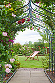 A garden with a rose arch, and a deck chair.