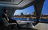 Mann sitz in einer modernen virtuellen Wohnung und schaut auf die Hafenskyline, Hamburg, Deutschland