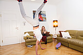 Young couple at home, doing a handstand, Fooling around