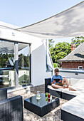 young guy with iPad on the roof top of a modern sigle-family house in Hamburg, north Germany, Germany