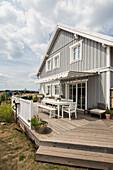 Graues zweistöckiges Einfamilienhaus mit Terrasse im nordischen Stil und Holzfassade, Korbach, Hessen, Deutschland, Europa