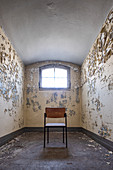 Old prison cell with peeling paint and chair, former district court prison in Berlin Koepenick, Germany