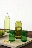 Grüne Gläser und grüne Flasche als Vase