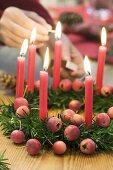 Lighting candles on Christmas wreath