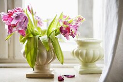 Wilted tulips in a ceramic vase
