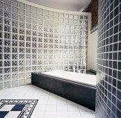 Loft-Badezimmer mit Wanne in steinverkleidetem Podest vor gebogener Glasbaustein-Wand und traditionellem Fliesenmuster am Boden