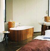 Das Bad im Schlafraum mit freistehender, holzverkleideter Badewanne und Holzsäule mit zwei Waschbecken