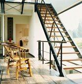 Einläufige Stahlholztreppe vor Fensterfront und hölzerne Armlehnstühle auf altem Dielenboden