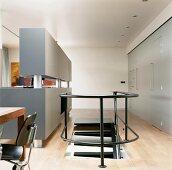 Treppenaufgang zwischen Schrankwand und offener, grauer Einbauküche