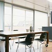 Moderner Esstisch auf Rollen und schwarze Stühle vor der Fensterfront im offenen Wohnraum