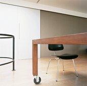 Schwarzer Stuhl mit Stahlrohrgestell an modernem Holztisch mit Rollen