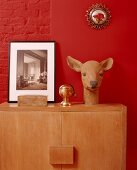 Deer's head sculpture and black and white photo on cabinet against bright red wall