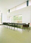 Minimalistischer Wohnraum - langer schwebender Esstisch mit Designer Stühlen und durchgehender Sitzbank vor Panoramafenster