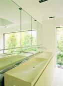 Aus Mineralwerkstoff in einem Guss geformter lindgrüner Waschtisch mit Wandarmaturen aus der Spiegelfläche