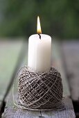 Burning candle in a ball of string
