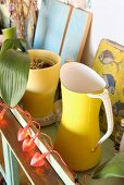 A yellow jug next to a yellow flowerpot