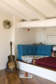 A guitar next to a raised seating corner in an attic room