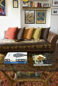 Leather sofa with colored pillows and glass top coffee table