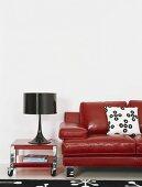 Eine rote Ledercouch neben schwarzer Tischlampe auf einem roten Couchtisch auf Rollen